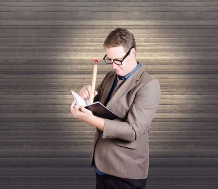 organisational: Male administration clerk wearing geek glasses pencilling in dates and meeting notes in a quirky organisational concept. On wooden office interior copyspace Stock Photo