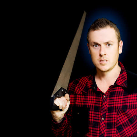threateningly: Snarling frustrated angry working man holding a sharp steel saw threateningly above his head on a black studio background Stock Photo