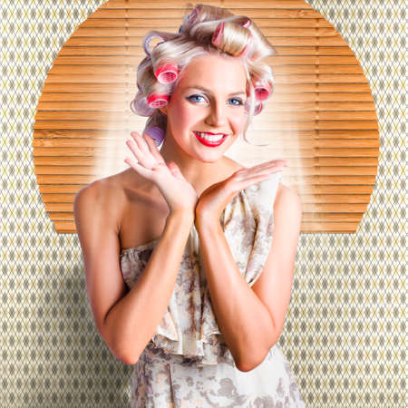 stylish hair: Smiling Stylish Vintage Blonde Woman In An Off The Shoulder Summer Dress Standing In A Classic Hairdresser With New Retro Hair Style In Large Hair Curlers Stock Photo