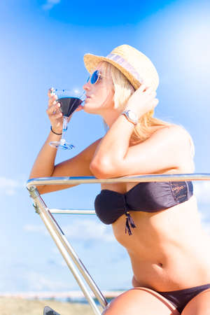 affluence: Rich Portrait Of Affluence And Wealth Sees A Blonde Lady Wearing Summertime Hat Drinking A Pina Colada Cocktail Beverage On A Boat In A Sip Of Ocean Paradise
