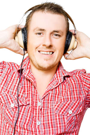 ear checked: Young man listening to music with his hands raised to his headphones as he smiles in pleasure and enjoyment isolated on white Stock Photo
