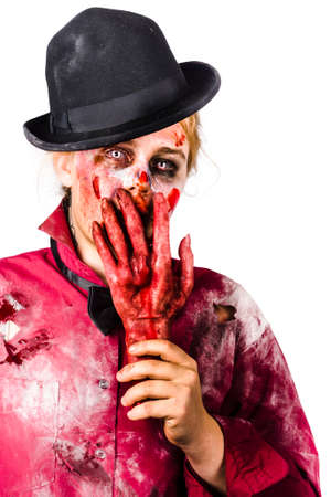 horrific: Creepy isolated portrait of a shocked female zombie covering mouth with severed human hand. Dead silence