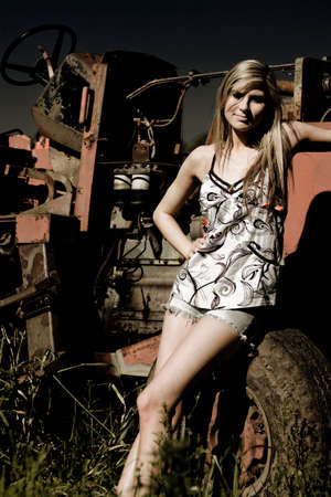 teenaged girls: A Rural Lady Sits On A Tractor Wheel After A Hard Days Work On Her Outback Farm In Dark Agriculture