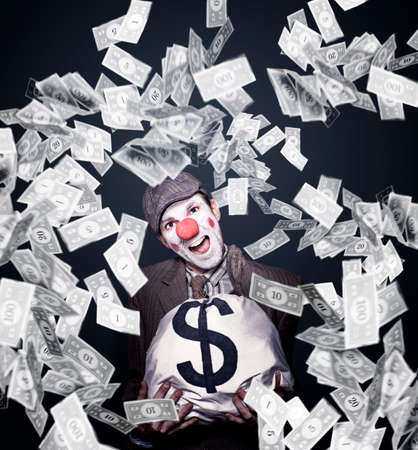 money concept: Excited Clown Holding A Dollar Money Bag Stuffed With Cash While Laughing All The Way To The Bank Stock Photo