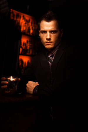 brawl: Handsome Tough Young Man With A Serious Look Standing In A Dark Bar With A Drink In A Bar Room Brawl And Fight Club Conceptual Stock Photo