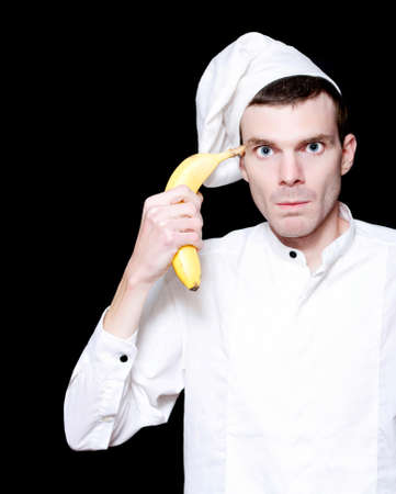 crazed: Crazy Kitchen Cook Going Fruity With A Banana In Hand While Under Hospitality Stress Over Black Stock Photo