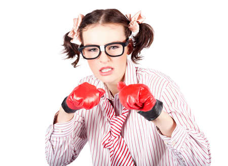 Fun image of a young woman in nerdy glasses and pigtails gritting her teeth in determinarion or agression wearing a pair of red boxing gloves and holding her fists in the defensive position