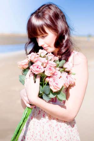 mujer con rosas: Una mujer enamorada de rosas Sostiene Un Ramo rosado cerca de su corazón con una Cariñoso Abrazo En un cuadro perfecto de San Valentín Día Pareja