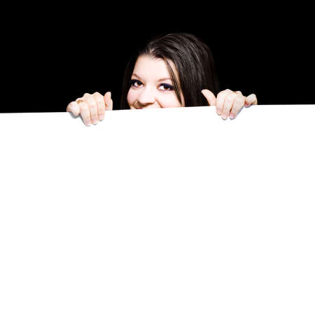 peeping: Young woman peeping over the top of a blank white placard that she is holding in her hands ready for your advertisement, promotion, announcement or marketing text