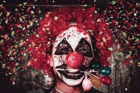 clown nose: Horizontal close-up portrait on the face of a mad carnival clown holding balloon cake decoration in mouth under a fall of confetti. Celebrating Halloween