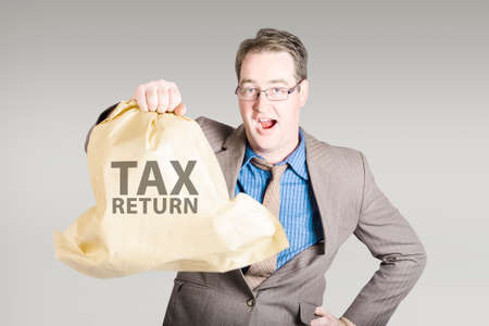 refunds: Business man holding income tax return with a happy expression of surprise. Big refund concept