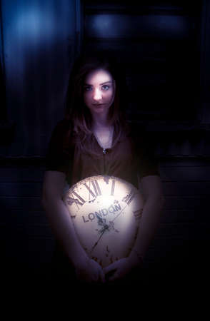 moody: Woman Holding A Large London Antique Clock Standing In The Dark Shadows.  Lighting Is Moody Representing Night Time