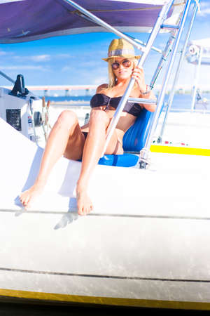 speedboat: Cute Young Woman On A Travel Tour Of Australia Sits In A White Speedboat Wearing Bikini And Sunnies In A Voyage Tourism And Vacation Sight Seeing Conceptual Stock Photo