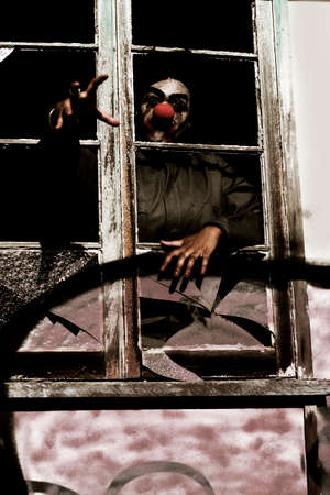 appalling: Reaching Out With Spine Chilling Terror A Killer Clown Grasps Through A Broken Window At The House Of Horrors