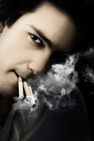 sombre: Dark Portrait On The Face Of An Addicted Male Tobacco Smoker, Puffing On Three Cigarettes In A Depiction Of Addiction And Dependency From Chronic Work Stress
