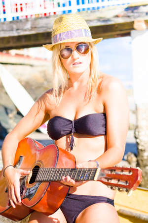 leisurely: Beautiful Sunglasses Girl Playing Guitar Outdoors In A Leisurely Performance Of Recreation And Musical Enjoyment Stock Photo