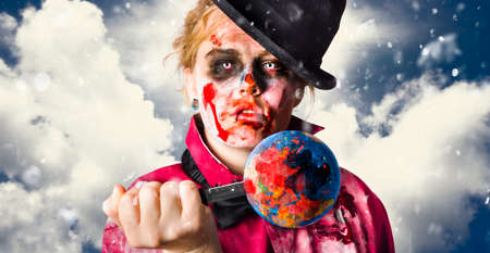 stabbing: Environmental concept of a zombie stabbing a globe of the world with blood stains when killing the planet with global pollution and destruction