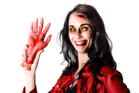 hand in hand: Smiling zombie woman holding a bloody severed hand when welcoming you to halloween Stock Photo