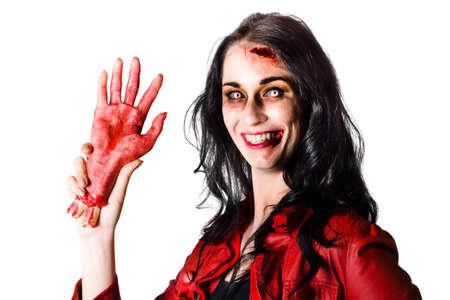 hemorragias: Sonriente mujer zombie celebración de una mano cortada sangrienta cuando darle la bienvenida a Halloween