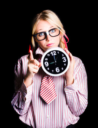 brainy: Brainy time management supervisor pointing to copyspace with dark clock in hand when gesturing time up Stock Photo