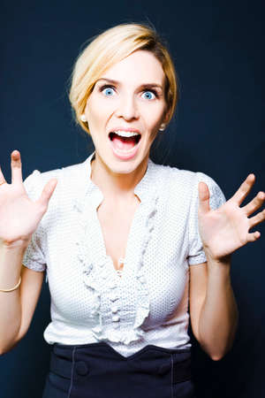 overwrought: Funny portrait of an attractive blonde business woman with her hands raised screaming in wide-eyed terror in a business conceptual for challenge, issues and problems, on black