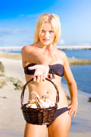 teases: An Attractive Young Bikini Woman Teases With Her Basket Of Collected Sea Shells With A Sassy And Flirtatious Expression With Blue Sky And Ocean Shore Background Stock Photo