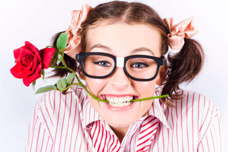 depiction: Portrait Of Geeky Young Woman Wearing Nerd Glasses Holding Rose In His Mouth In A Depiction Of Valentines Day Love Stock Photo