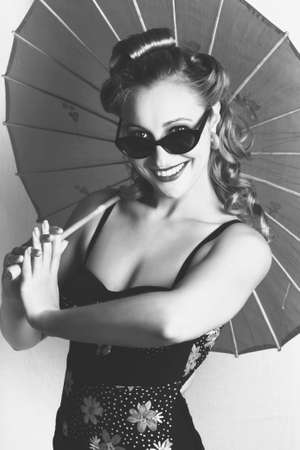 panache: Black And White Portrait Of A Smiling Vintage Lady With Classical Hair, Makeup And Fashion Dancing With A Retro Umbrella