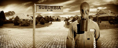 suburbia: Man wearing gasmask on a suburban street next to Suburbia street sign in a depiction of the struggle and conflict in modern day life