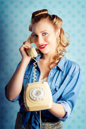 converse: Beautiful Young Pin-Up Woman With Sixties Era Make-Up And Classical Hairstyle Posing With Retro Telephone While In Gossip Converse