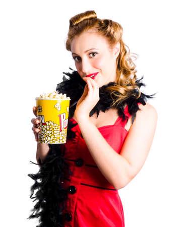 robo: Atractiva mujer rubia con rizos en vestido rojo y negro estola celebración de una gran caja de palomitas de maíz en el fondo blanco Foto de archivo