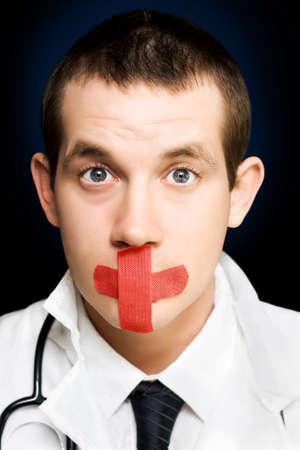 silencio: Foto de cerca en la cara de un médico guapo sorprendido en silencio, con la ayuda banda roja en la cara en una representación de una conspiración de encubrimiento de la salud