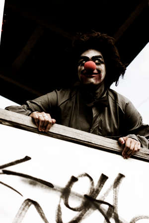 ghoulish: Creepy Clown Standing On A Verandah With A Scary Smile During A Halloween Trick Or Treat Session