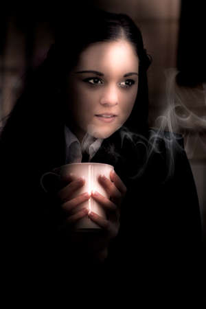 evaporate: Atmospheric And Lowkey Portrait Of An Attractive Young Brunette Woman Snuggling Up To A Warm Hot Drink As Vapors Of Steam Evaporate Into The Cold Winter Night