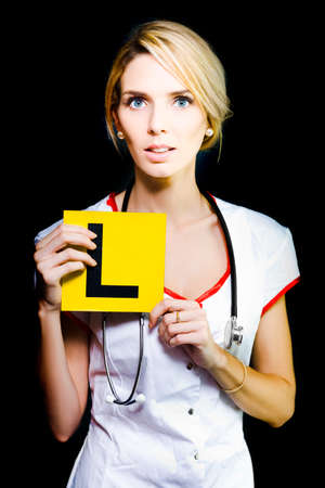 medical career: Beware of a beautiful blonde female novice nurse or medical student with a look of trepidation on her face at her new career standing holding an L sign denoting Learner Stock Photo
