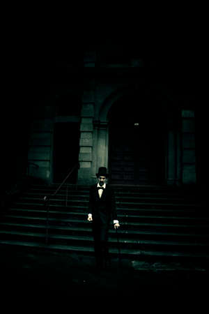 horrifying: A Horror Scene See A Vintage Man Wearing Top Hat And Formal Attire Standing On One Leg Lurking Out The Front Of Old Building In The Shadows Of Darkness