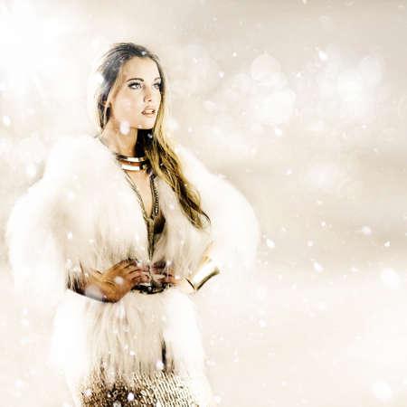 mujer elegante: mujer elegante con abrigo de piel con las manos en las caderas, con la nieve cayendo a su alrededor en un concepto de tiempo de invierno Foto de archivo