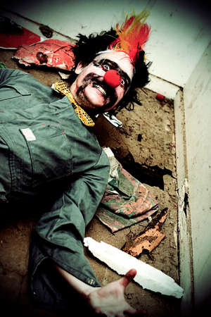 horrific: Mr Sleepy The Creepy Clown Lays On A Holey Rubbish Littered Floor With A Horrific Smile Across His Frightening Face Stock Photo