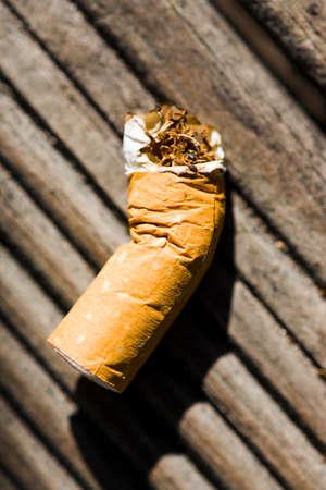botar basura: Colilla desechados Aire libre en el suelo de una pasarela de madera en un acto imprudente de Tirar basura Foto de archivo