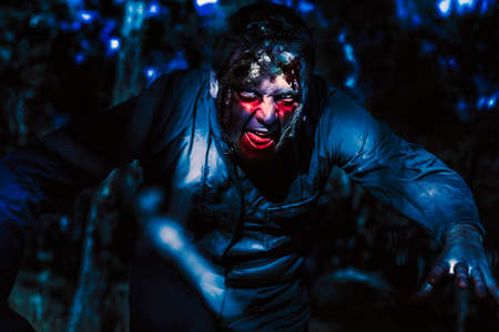 male face: Dark halloween photograph on the face of an evil zombie man creeping though black shadows at the dead on night