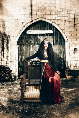 sombre: Beautiful netherworld woman in crowned jewelry sitting by the gates of heaven and hell wearing elegant royal garb and gold crown. Forever in never never land