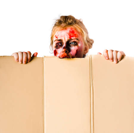 ghoulish: A woman in ghoulish undead make up peeking from behind a blank card board cover