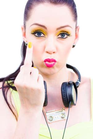 auriculares dj: En un gesto ofensivo anti sociales de Bad Manners Un rebelde del punk rock de la muchacha el uso de auriculares solutos su dedo medio en A DJ grosero o concepto Música enojado Foto de archivo