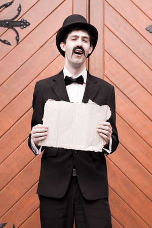 chuckling: Man In Black Suit Standing In Front Of Wooden Door Laughing While Holding A Blank Sign In A Sign Of Vintage Humor