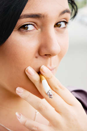 guilty pleasure: Young Woman Inhaling Smoke From A Lit Cigarette With A Mischievous Look Of Guilt Stock Photo
