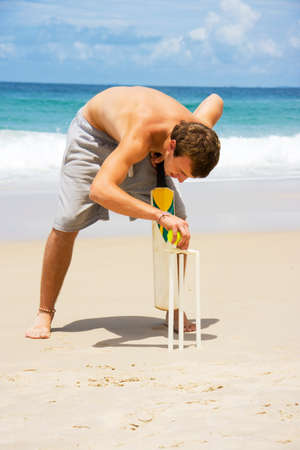 cricket stump: Young man with bare chest and shorts balancing bails on beach cricket stumps with sea in background.