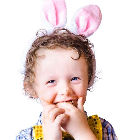 huevo blanco: Chico con orejas de conejo color rosa Pascua rematando un huevo de chocolate en el fondo blanco