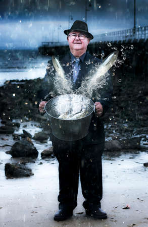 abundance: Senior Man Holding A Bucket Filled With Splashing Water And Jumping Fish Standing On A Seaside Shoreline In A Depiction Of Plentitude And Abundance Stock Photo