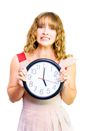 contorted: Attractive young blonde business woman clutches a clock showing the time as five oclock in a time to stop work conceptual of being out of time Stock Photo