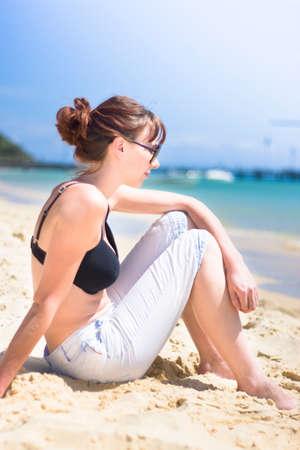 beach babe: Resting Beach Babe Woman Sitting On A Beach Shoreline Near The Ocean Edge Stock Photo
